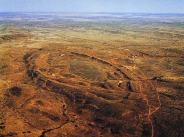 Aerial oblique view of the Telfer Dome in 1976, prior to the start of major excavations of the deposit. Image is drawn from the archives of Newcrest Mining Limited, and was published in Ferguson et al. (2005) - 'Mineral Occurrences and Exploration Potential of the Paterson Area' - Report 97 of the GSWA.