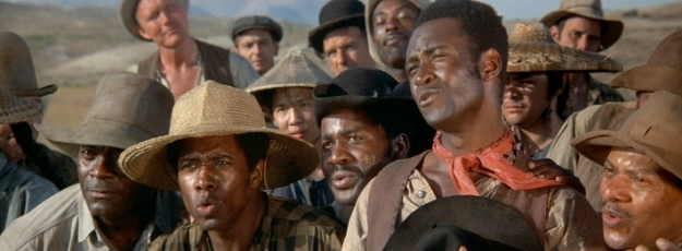 "Bart and his fellow convicts responding to overseer Lyle's entreaty: ""Now come on boys, where's your spirit? I don't hear no singin'. When you were slaves, you sang like birds. Go on. How 'bout a good ole nigger work song?"" Still image taken from Mel Brooks' 1974 comedy ""Blazing Saddles""."